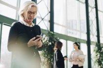 Empresária sênior usando telefone celular enquanto os colegas se comunicam em segundo plano — Fotografia de Stock