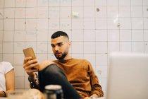 Jeune homme d'affaires utilisant un téléphone intelligent assis par une collègue féminine contre un mur au bureau — Photo de stock