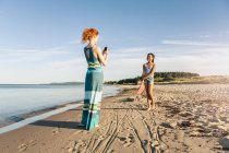Woman photographing daughter standing on shore at beach against sky — Stock Photo