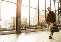 Senior maschili pendolari a piedi con i bagagli alla stazione della ferrovia — Foto stock