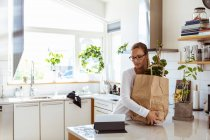 Woman holding paper bag while looking at digital tablet in kitchen — Stock Photo