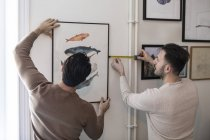 Visão traseira do casal gay pendurado pintura na parede em casa — Fotografia de Stock