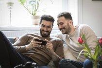 Jovens sorridentes olhando para o telefone inteligente enquanto sentados no sofá em casa — Fotografia de Stock