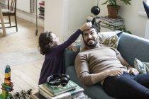 Vue grand angle de la fille gardant bloc jouet sur la tête du père couché sur le canapé à la maison — Photo de stock