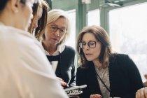 Mulheres de negócios olhando para o arquivo em reunião — Fotografia de Stock