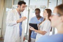 Уверенные многоэтнические медсестры и врачи обсуждают цифровую таблетку в лобби в больнице — стоковое фото