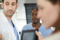 Мульти-етнічні працівники охорони здоров'я обговорюють цифровий планшет у вестибюлі в лікарні — стокове фото