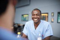 Sorridente infermiera maschile che parla con un collega alla mensa dell'ospedale — Foto stock