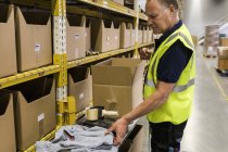 Side view of senior male worker packing merchandise in cardboard box at distribution warehouse — Stock Photo