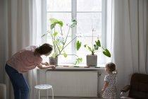 Hija ayuda a diseñador de moda medir la ventana con cinta métrica en casa - foto de stock