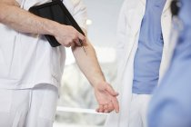 Midsection of male nurse gesturing while standing with coworkers at hospital — Stock Photo