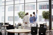 Visão traseira do enfermeiro a tomar selfie com a equipa médica no refeitório do hospital — Fotografia de Stock