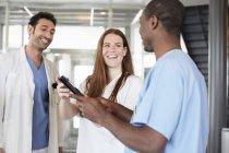 Assistenti sanitari multietnici sorridenti che discutono su tablet digitale mentre si trovano nella hall dell'ospedale — Foto stock