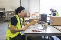 Уверенный молодой представитель мужской службы поддержки смотрит в сторону, сидя с ноутбуком за столом на складе — стоковое фото