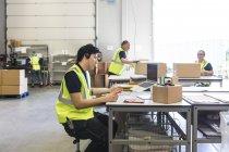 Junger Kundendienstmitarbeiter im Gespräch über Headset während der Mitarbeiter im Lager — Stockfoto