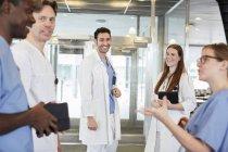 Equipe multi-ethnic de sorriso dos cuidados médicos que discutem na entrada no hospital — Fotografia de Stock