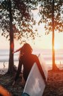 Rear view of mature woman with surfboard walking at beach during sunset — Photo de stock