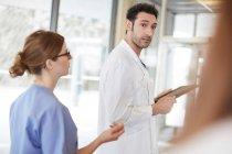 Молодой врач, держащий цифровую таблетку, глядя в сторону женщины-медсестры, стоящей в вестибюле в больнице — стоковое фото