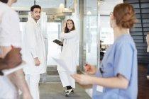 Trabajadores sanitarios multiétnicos discutiendo en el lobby en el hospital - foto de stock