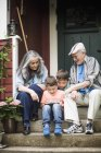 Grandparents and twin grandsons sitting at front stoop — Stock Photo