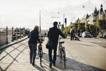 Vue arrière pleine longueur du couple aîné avec vélos marchant sur le trottoir en ville — Photo de stock