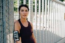 Retrato de deportista segura con teléfono inteligente y auriculares apoyados en la barandilla en el puente - foto de stock