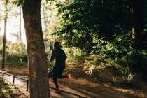 Full length of male athlete running on footpath in park — Stock Photo