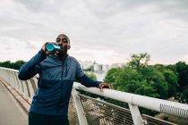 Retrato de esportista sedento bebendo de garrafa enquanto estava em pé na passarela contra o céu — Fotografia de Stock