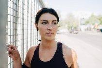 Young sportswoman looking away while listening music through earphone on bridge — Stock Photo