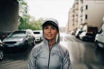 Portrait of confident female athlete in wet hooded jacket standing on street in city — Stock Photo