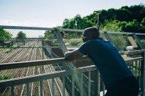 Esportista cansado olhando para longe enquanto se inclina em trilhos na ponte — Fotografia de Stock