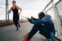 Спортсмен проведення мобільного телефону під час cheering спортсменка курсує місток — стокове фото