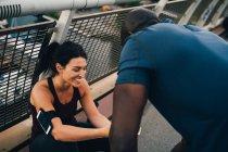 Atleta femenina mostrando teléfono móvil a deportista en pasarela - foto de stock