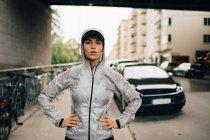Ritratto di atleta donna sicura di sé in giacca bagnata con cappuccio in piedi sul marciapiede in città — Foto stock
