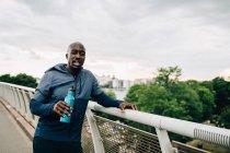 Retrato de esportista sedento segurando garrafa de água enquanto estava de pé por trilhos na passarela contra o céu — Fotografia de Stock