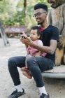 Petite fille à l'aide de téléphone portable assis avec père sur l'équipement de jeu extérieur au terrain de jeux — Photo de stock