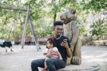 Père à l'aide de téléphone portable assis avec fille sur équipement de jeux en plein air — Photo de stock