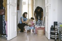 Daughter looking at mother and father packing luggage at home — Stock Photo