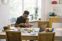 Молодой человек играет с дочерью, сидя за столом в доме — стоковое фото