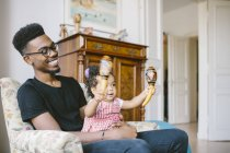 Baby girl holding maracas while sitting with happy father on armchair at home — Stock Photo