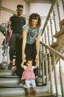 Mutter, die Hand in Hand der Tochter zu Schritten in Wohnung nach unten bewegen — Stockfoto
