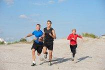 Jeunes amis, faire du jogging sur la plage — Photo de stock
