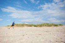 Vista laterale di giovane uomo che pareggia sulla spiaggia — Foto stock