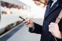 Міделю бізнесмен, за допомогою мобільного телефону на залізничний вокзал — стокове фото