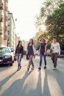 Pleine longueur des étudiants confiants de lycée marchant sur la rue de ville — Photo de stock