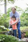 Father and son watering plants with can in back yard — Stock Photo