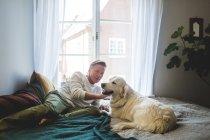 Senior homme caressant chien tout en s'appuyant sur le lit à la maison — Photo de stock