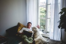 Senior man lying with dog while reading book on bed by window at home — Stock Photo