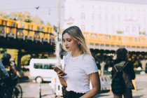 Young woman using mobile phone while walking by street in city — Stock Photo