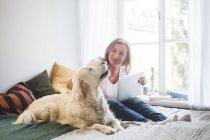 Liebevolle Seniorin berührt Hund, während sie Laptop zu Hause im Bett hält — Stockfoto